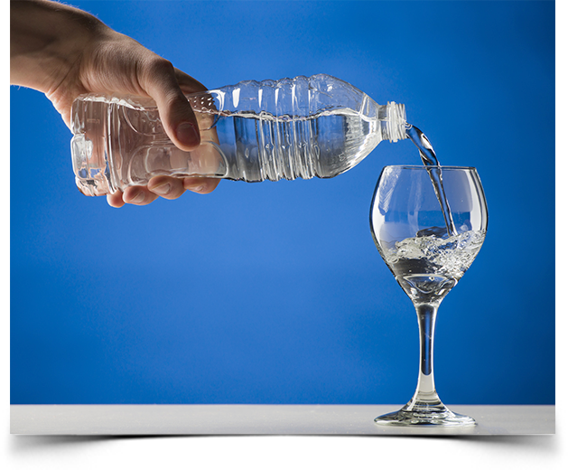 Pouring bottled alkaline water into a wine glass