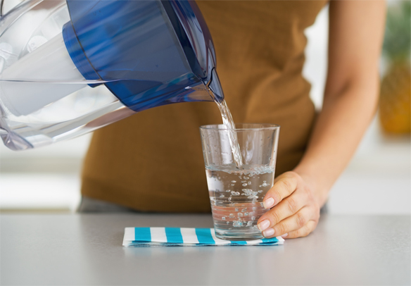 woman pouring filtered water into a glass